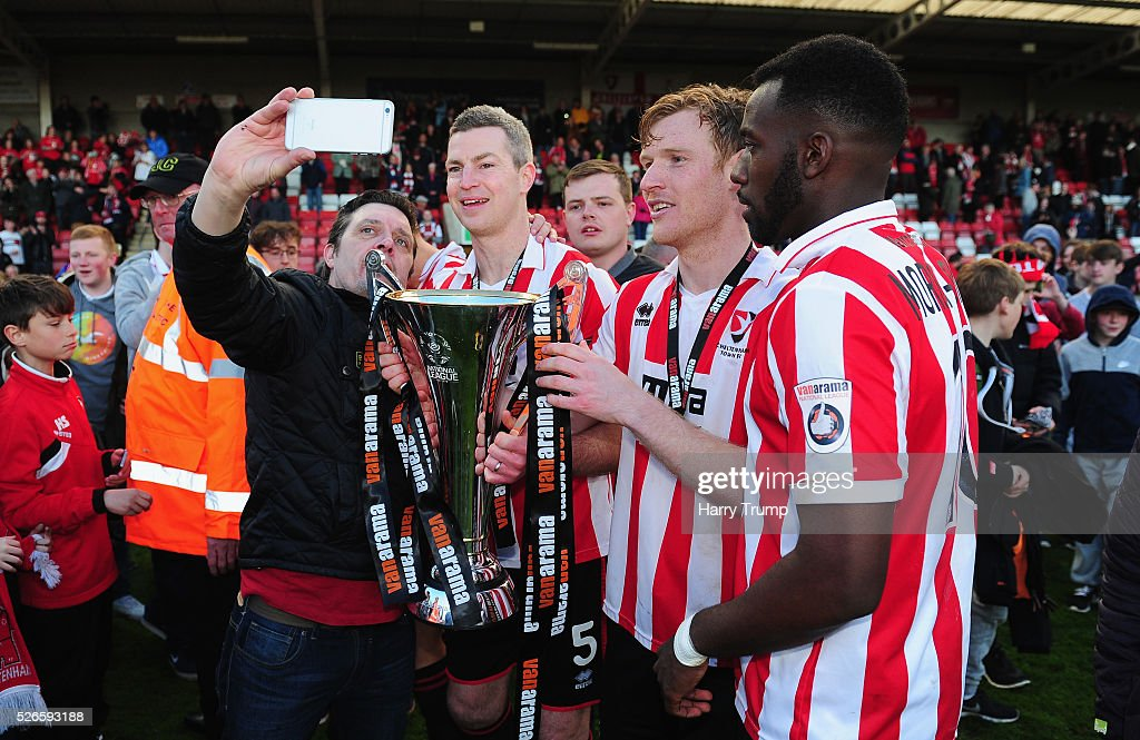 Aaron Downes(L), Kyle Storer and Amari Morgan-Smith of Cheltenham Town pose for a selfie with Cheltenham Town fans after being crowned Vanarama Conference Champions during the Vanarama Football Conference match between Cheltenham Town and Lincoln City at the World of Smile Stadium on April 30, 2016 in Cheltenham, England.