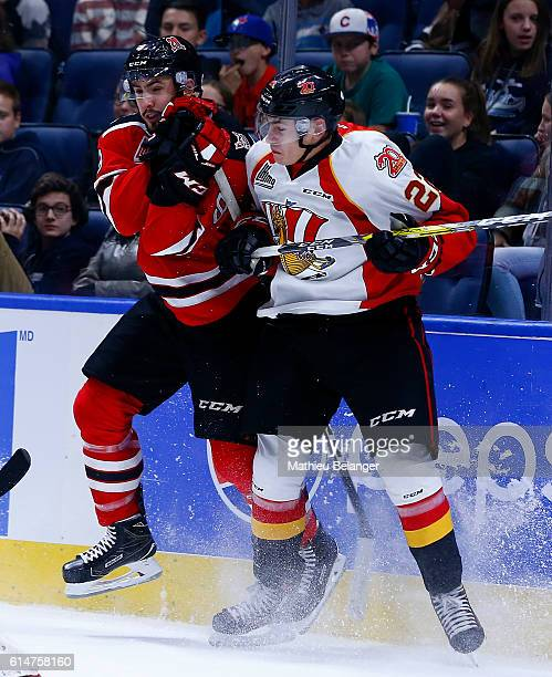 Aaron Dutra of the Quebec Remparts hits Shawn Element of the Baie Comeau Drakkar during their QMJHL hockey game at the Centre Videotron on October 14...