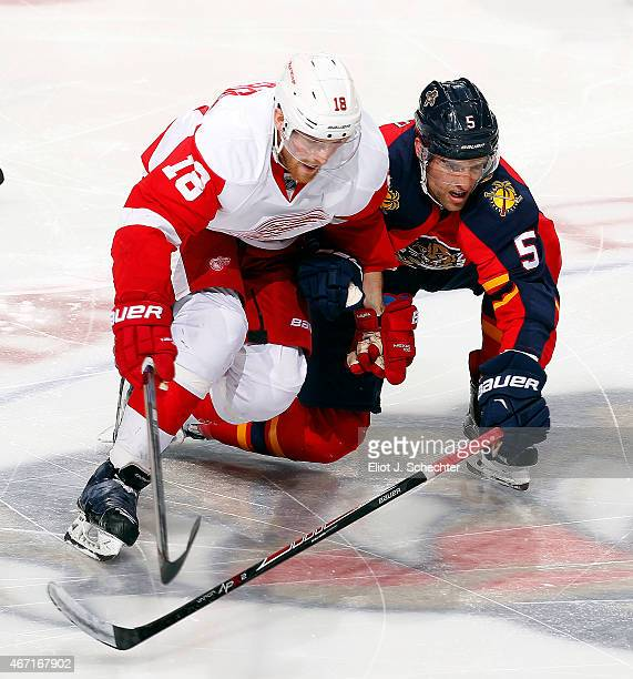 Aaron Ekblad of the Florida Panthers skates for possession against Joakim Andersson of the Detroit Red Wings at the BBT Center on March 19 2015 in...