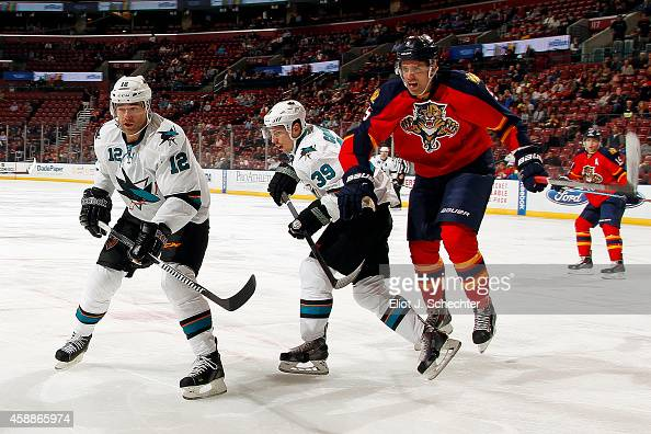 Aaron Ekblad of the Florida Panthers tangles with Patrick Marleau and Logan Couture of the San Jose Sharks at the BBT Center on November 11 2014 in...