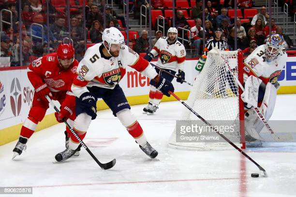 Aaron Ekblad of the Florida Panthers tries to control the puck next to Henrik Zetterberg of the Detroit Red Wings during the second period at Little...
