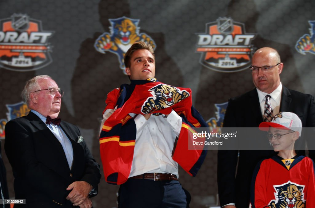 Aaron Ekblad puts on his jersey after being selected first overall by the Florida Panthers during the 2014 NHL Entry Draft at Wells Fargo Center on June 27, 2014 in Philadelphia, Pennsylvania.