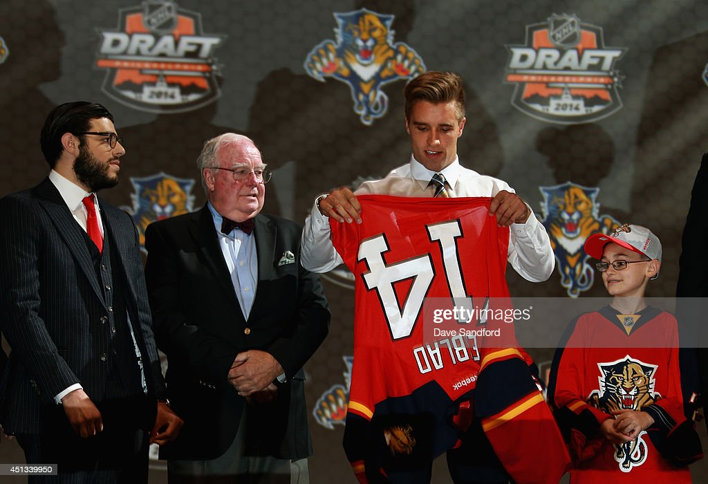 <a gi-track='captionPersonalityLinkClicked' href=/galleries/search?phrase=Aaron+Ekblad&family=editorial&specificpeople=8953211 ng-click='$event.stopPropagation()'>Aaron Ekblad</a> puts on his jersey after being selected first overall by the Florida Panthers during the 2014 NHL Entry Draft at Wells Fargo Center on June 27, 2014 in Philadelphia, Pennsylvania.