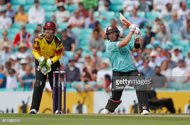 Aaron Finch of Surrey hits a boundary as Somerset wicket keeper Steven Davies looks on during the NatWest T20 Blast match at The Kia Oval on July 9...