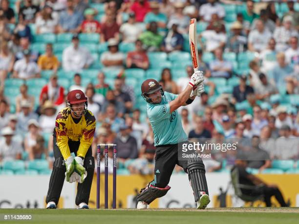 Aaron Finch of Surrey hits a six as Somerset wicket keeper Steven Davies looks on during the NatWest T20 Blast match at The Kia Oval on July 9 2017...