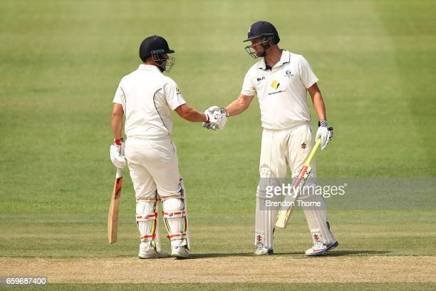 Aaron Finch of the Bushrangers celebrates scoring his half century with team mate Cameron White during the Sheffield Shield final between Victoria...