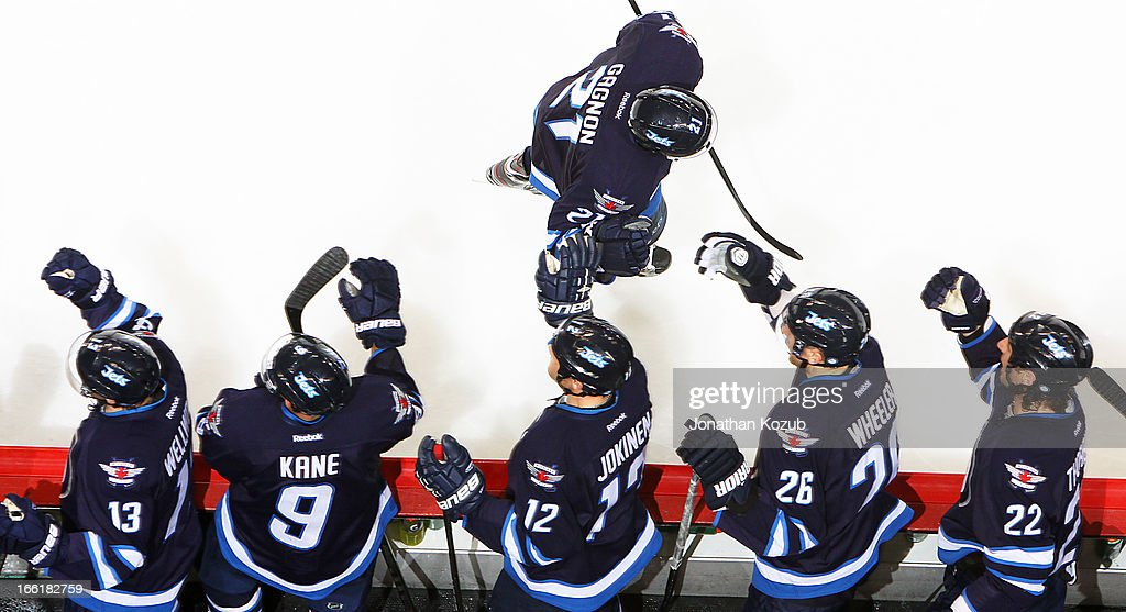 Aaron Gagnon #21 of the Winnipeg Jets is congratulated by teammates on the bench following his first career NHL goal in the second period against the Buffalo Sabres at the MTS Centre on April 9, 2013 in Winnipeg, Manitoba, Canada.