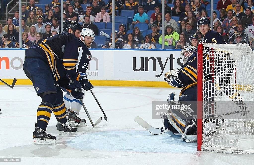 Aaron Gagnon #21 of the Winnipeg Jets scores a second period goal against Jhonas Enroth #1 of the Buffalo Sabres while defended by Mike Weber #6 of the Sabres on April 22, 2013 at the First Niagara Center in Buffalo, New York.