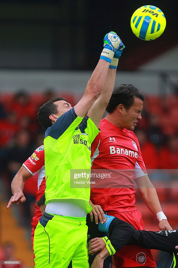 Aaron Galindo of Toluca struggles for the ball with Agustin Marchesin goalkeeper of Santos Laguna during a match between Toluca and Santos Laguna as part of 6th round Clausura 2015 Liga MX at Nemesio Diez Stadium on February 15, 2015 in Toluca, Mexico.