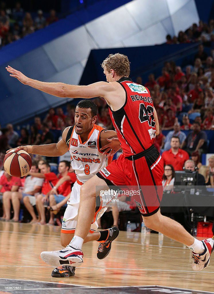 Aaron Grabau of the Taipans looks to drive past Shawn Redhage of the Wildcats during the round 23 NBL match between the Perth Wildcats and the Cairns Taipans at Perth Arena on March 17, 2013 in Perth, Australia.