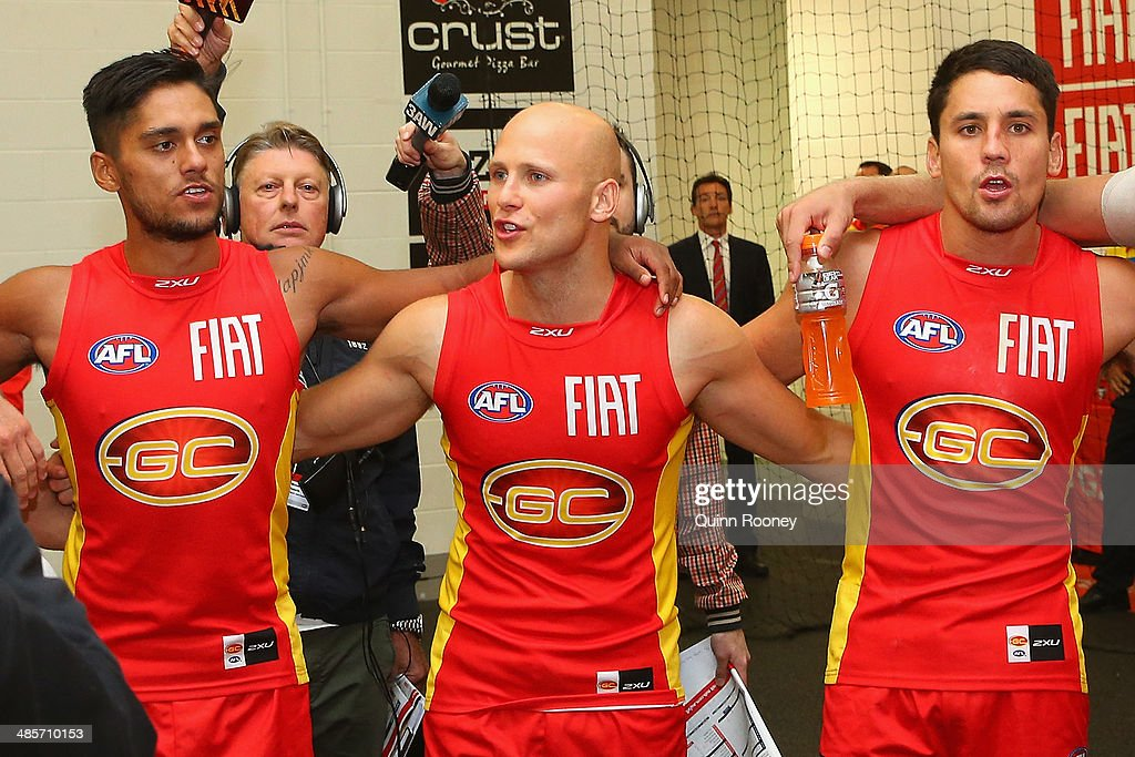 Aaron Hall, Gary Ablett and Greg Broughton of the Suns sing the song in the rooms after winning the round five AFL match between the Melbourne Demons and the Gold Coast Suns at Melbourne Cricket Ground on April 20, 2014 in Melbourne, Australia.
