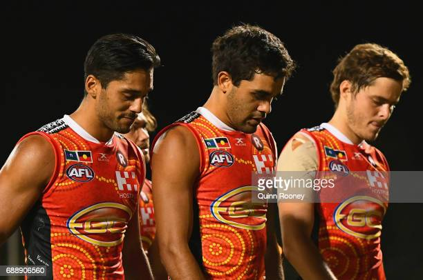 Aaron Hall Jack Martin and Kade Kolodjashnij of the Suns look dejected after losing the round ten AFL match between the Melbourne Demons and the Gold...