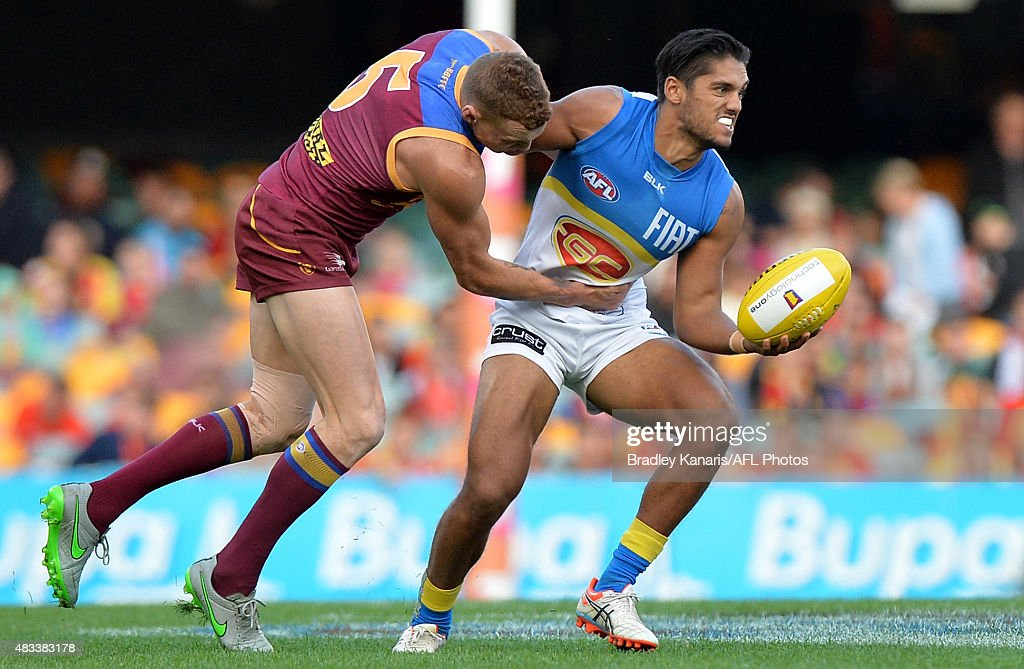 Aaron Hall of the Suns and Mitch Robinson of the Lions challenge for the ball during the round 19 AFL match between the Brisbane Lions and the Gold...