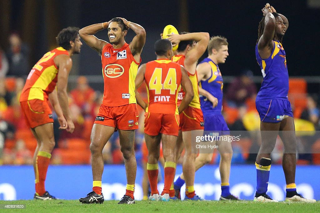 Aaron Hall of the Suns and Nic Naitanui of the Eagles react after a draw during the round 18 AFL match between the Gold Coast Suns and the West Coast...