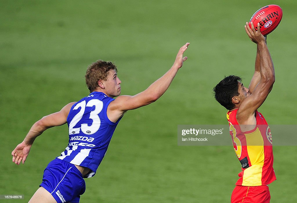Aaron Hall of the Suns catches the ball ahead of Kieran Harper of the Kangaroos during the round two AFL NAB Cup match between the Gold Coast Suns...