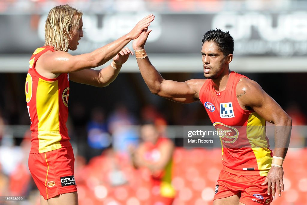 Aaron Hall of the Suns celebrates kicking a goal with Matt Shaw during the round six AFL match between the Gold Coast Suns and the Greater Western...