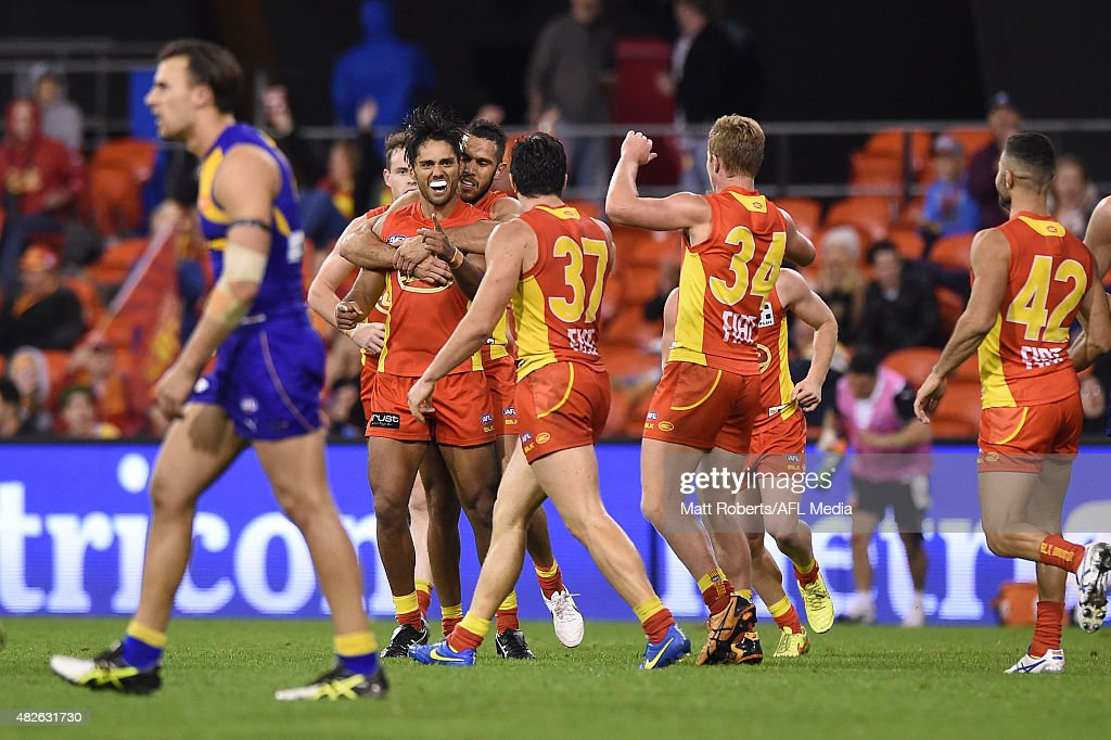 Aaron Hall of the Suns celebrates kicking a goal with team mates during the round 18 AFL match between the Gold Coast Suns and the West Coast Eagles...