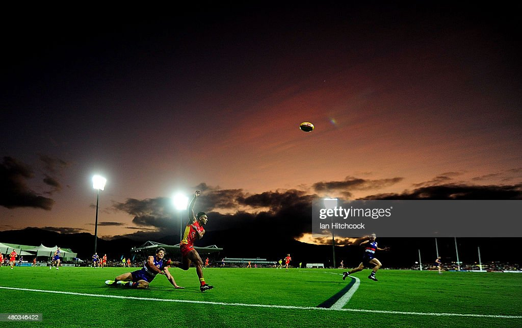 Aaron Hall of the Suns gets a kick away despite the tackle of Will Minson of the Bulldogs during the round 15 AFL match between the Western Bulldogs and the Gold Coast Suns at Cazaly's Stadium on July 11, 2015 in Cairns, Australia.