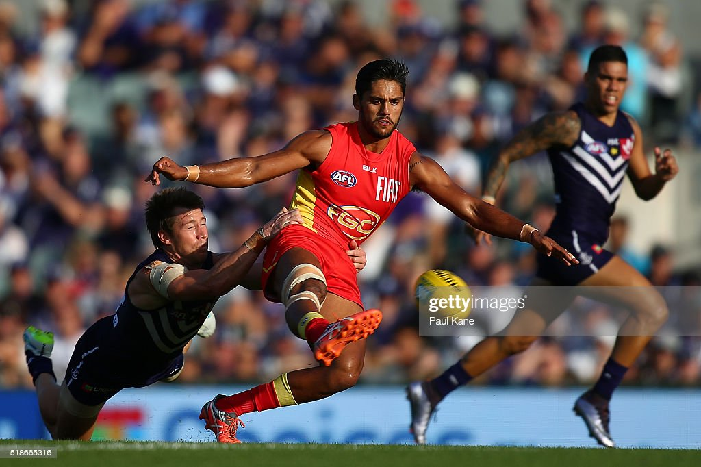 Aaron Hall of the Suns gets his kick away while being tackled by Lee Spurr of the Dockers during the round two AFL match between the Fremantle...