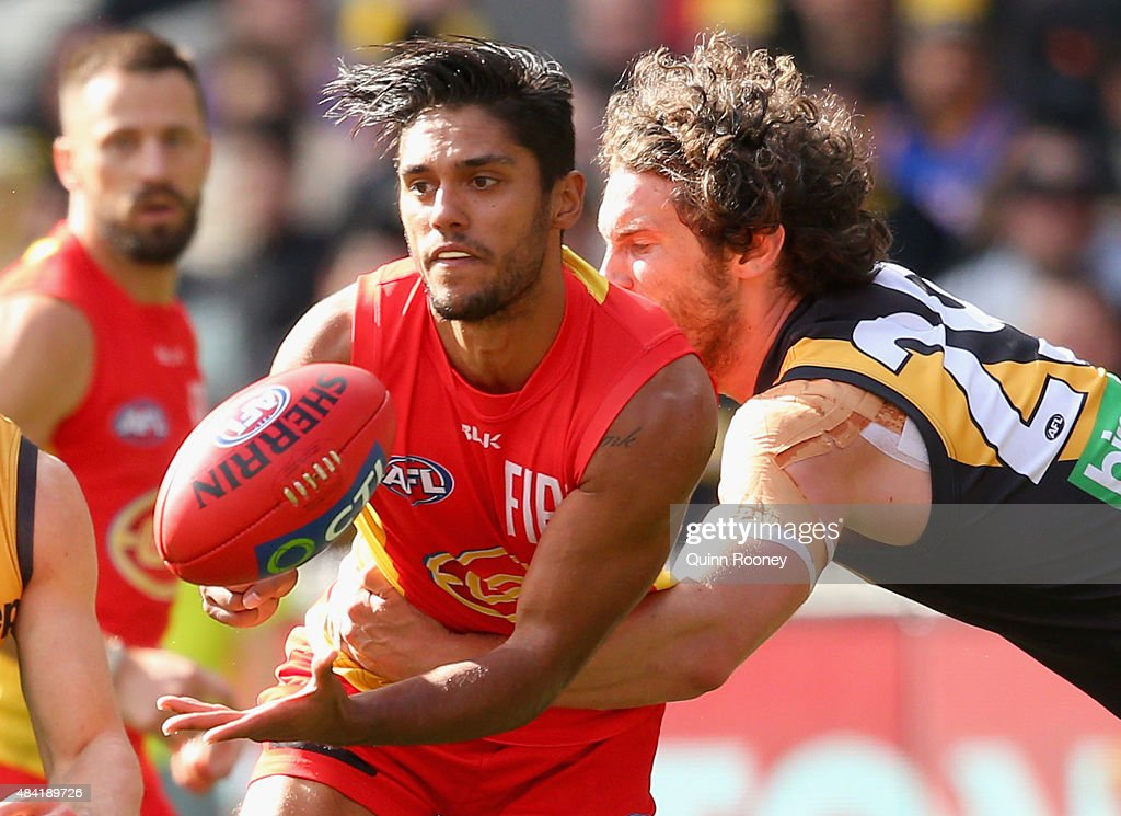 Aaron Hall of the Suns handballs whilst being tackled by Tyrone Vickery of the Tigers during the round 20 AFL match between the Richmond Tigers and...