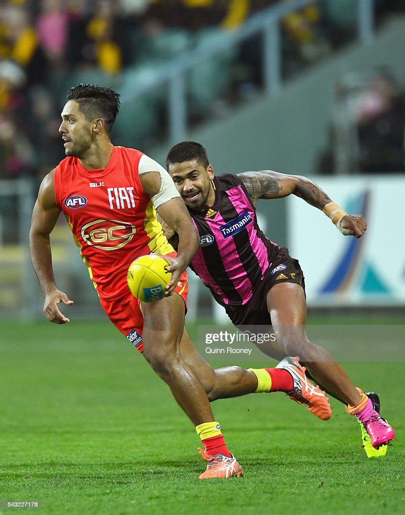 Aaron Hall of the Suns is chased by Bradley Hill of the Hawks during the round 14 AFL match between the Hawthorn Hawks and the Gold Coast Suns at...