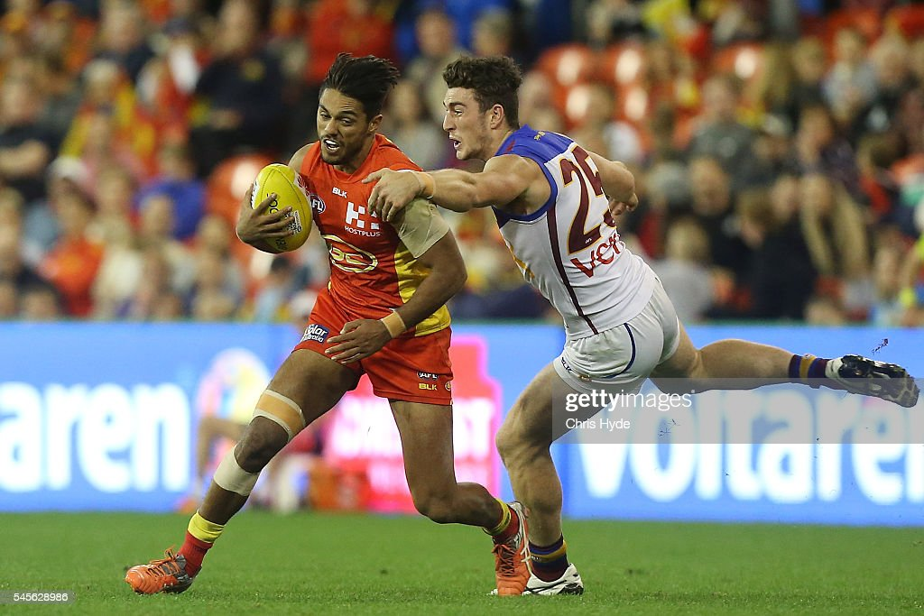Aaron Hall of the Suns is tackled by Daniel McStay of the Lions during the round 16 AFL match between the Gold Coast Suns and the Brisbane Lions at...