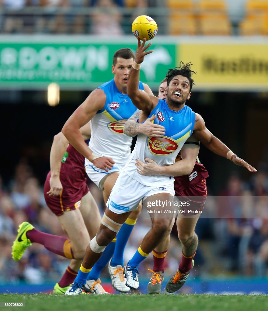 Aaron Hall of the Suns is tackled by Dayne Beams of the Lions during the 2017 AFL round 21 match between the Brisbane Lions and the Gold Coast Suns at the Gabba on August 12, 2017 in Brisbane, Australia.