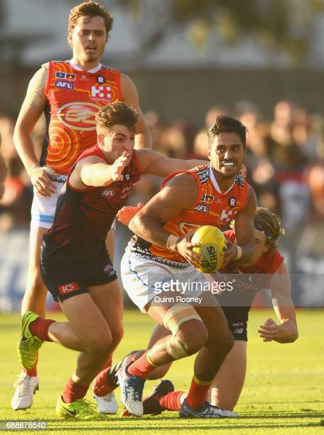 Aaron Hall of the Suns is tackled by Jack Viney and Jayden Hunt of the Demons during the round ten AFL match between the Melbourne Demons and the...