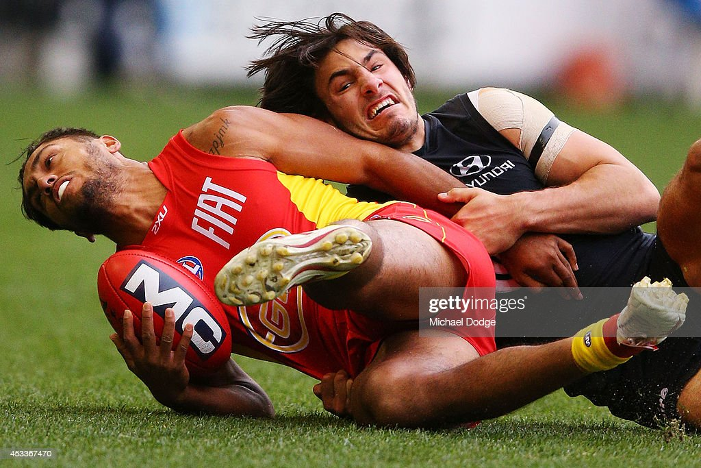 Aaron Hall of the Suns is tackled by Troy Menzel of the Blues during the round 20 AFL match between the Carlton Blues and the GOld Coast Titans at...