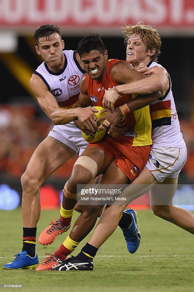 Aaron Hall of the Suns is tackled during the NAB Challenge AFL match between the Gold Coast Suns and the Adelaide Crows at Metricon Stadium on March...