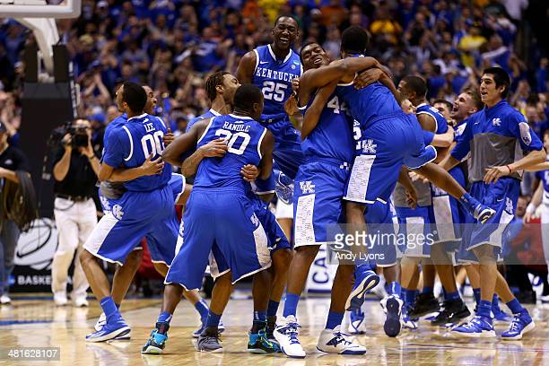 Aaron Harrison of the Kentucky Wildcats celebrates with teammates Julius Randle and Dakari Johnson after defeating the Michigan Wolverines 75 to 72...