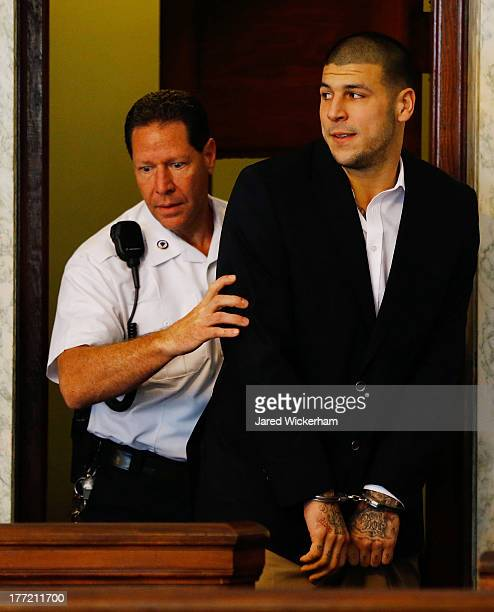 Aaron Hernandez is escorted into the courtroom of the Attleboro District Court for his hearing on August 22 2013 in North Attleboro Massachusetts...