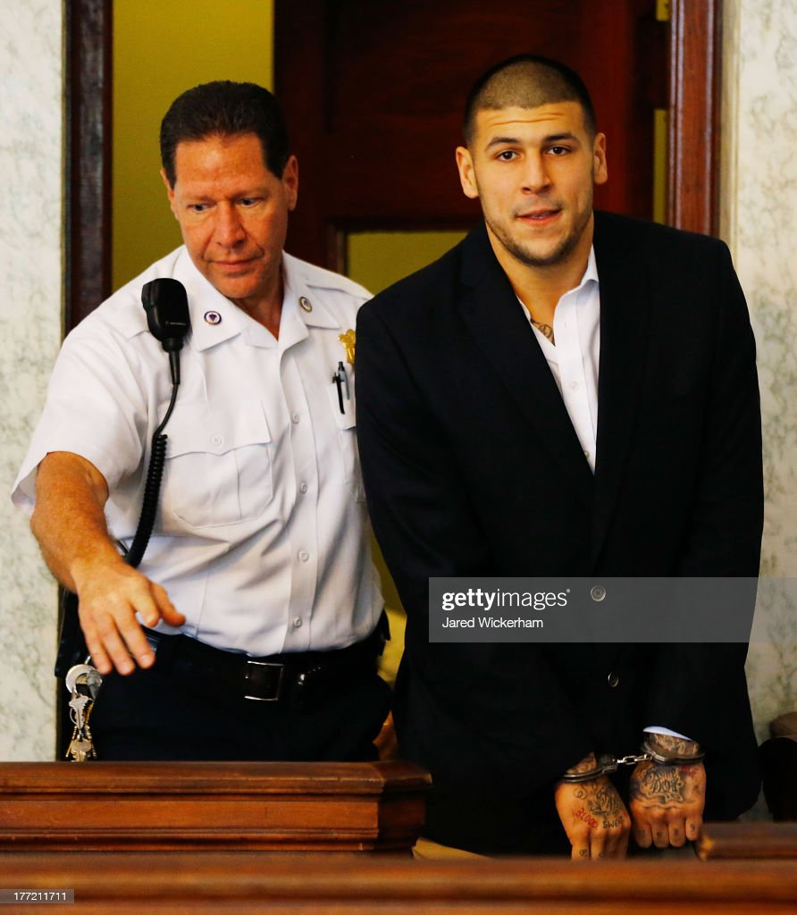 Aaron Hernandez is escorted into the courtroom of the Attleboro District Court for his hearing on August 22, 2013 in North Attleboro, Massachusetts. Former New England Patriot Aaron Hernandez has been indicted on a first-degree murder charge for the death of Odin Lloyd.