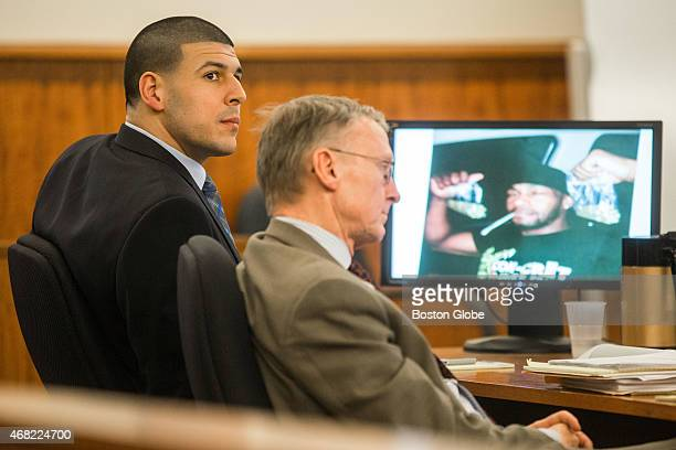 Aaron Hernandez left listens to testimony next to his attorney Charles Rankin as a photo of witness Darryl Hodge is displayed during the murder trial...