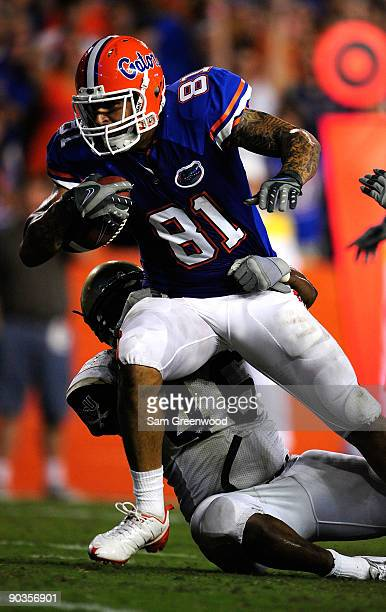 Aaron Hernandez of the Florida Gators runs for a touchdown over Fred Godfrey of the Charleston Southern Buccaneers during the game at Ben Hill...
