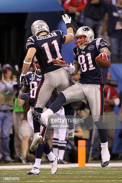 Aaron Hernandez of the New England Patriots celebrates with his teammates Julian Edelman after catching a 12 yard touchdown pass from Tom Brady in...