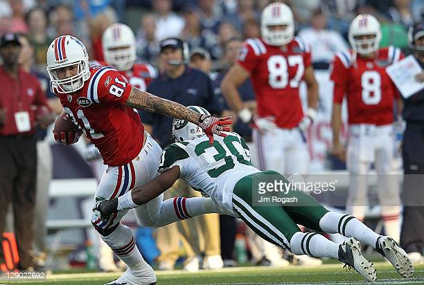 Aaron Hernandez of the New England Patriots gains yards as Donald Strickland of the New York Jets defends in the second half at Gillette Stadium on...