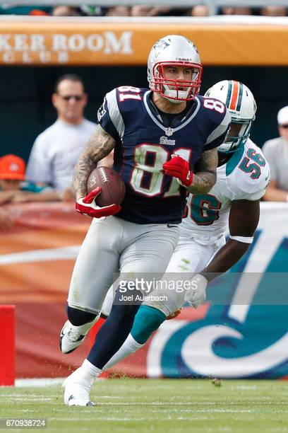 Aaron Hernandez of the New England Patriots runs with the ball against the Miami Dolphins on December 2 2012 at Sun Life Stadium in Miami Gardens...
