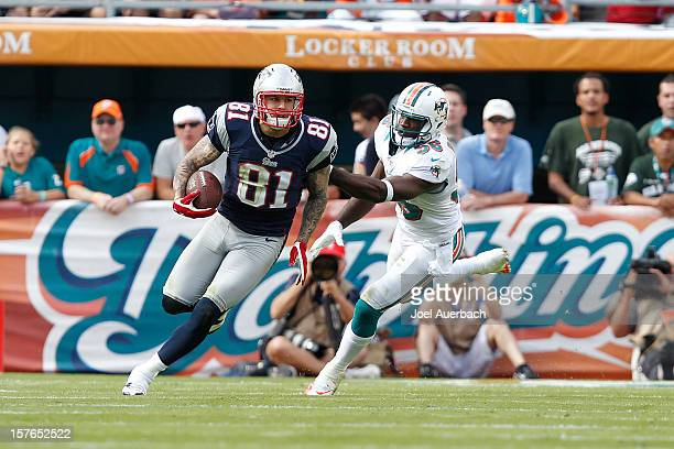 Aaron Hernandez of the New England Patriots runs with the ball while being defended by Kevin Burnett of the Miami Dolphins on December 2 2012 at Sun...