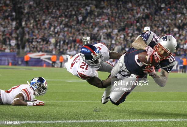 Aaron Hernandez of the New England Patriots scores against the defense of Kenny Phillips of the New York Giants at Gillette Stadium in the second...