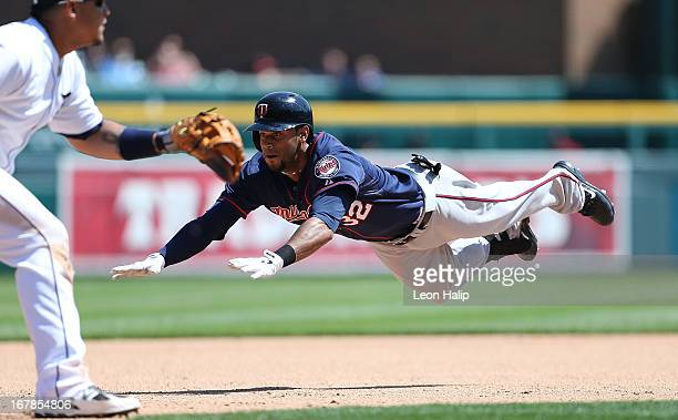 Aaron Hicks of the Minnesota Twins dives head first into third base for a triple during the seventh inning of the game against the Detroit Tigers at...