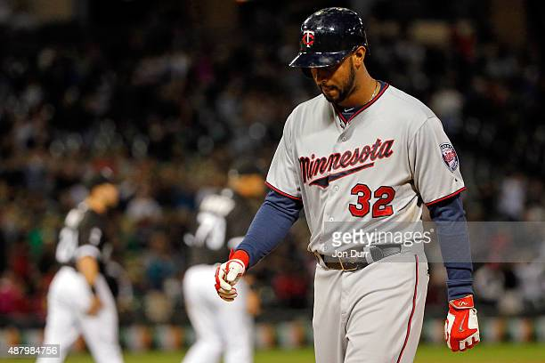 Aaron Hicks of the Minnesota Twins walks off the field after flying out to end the game against the Chicago White Sox at US Cellular Field on...