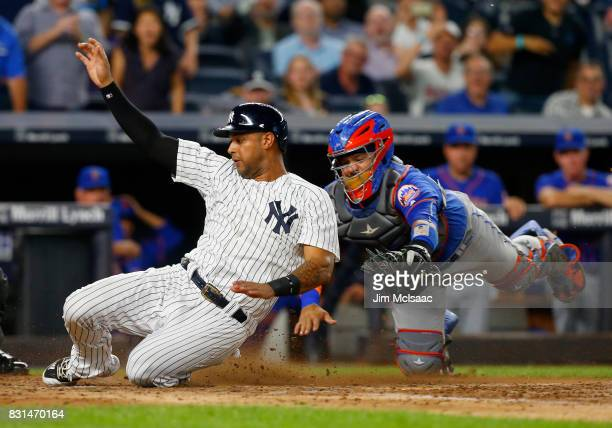 Aaron Hicks of the New York Yankees beats the tag from Rene Rivera of the New York Mets to score a run in the fourth inning at Yankee Stadium on...