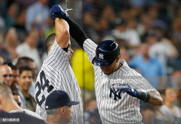 Aaron Hicks of the New York Yankees celebrates his eighth inning home run against the New York Mets with teammate Gary Sanchez at Yankee Stadium on...