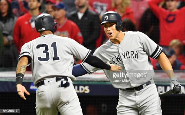Aaron Hicks of the New York Yankees celebrates with Aaron Judge after scoring on a two RBI single by Brett Gardner in the ninth inning against the...