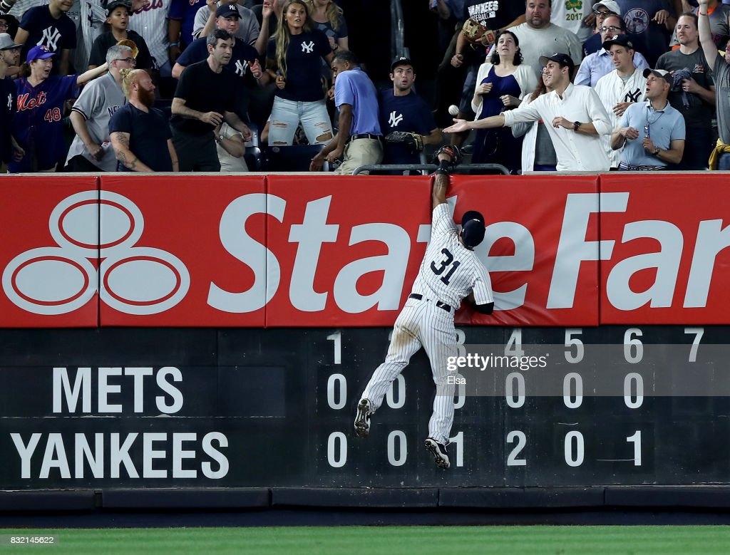 Aaron Hicks #31 of the New York Yankees heads for the wall as a hit by Dominic Smith of the New York Mets flies into the stands for a two run home run in the seven inning during interleague play on August 15, 2017 at Yankee Stadium in the Bronx borough of New York City.