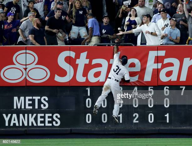 Aaron Hicks of the New York Yankees heads for the wall as a hit by Dominic Smith of the New York Mets flies into the stands for a two run home run in...