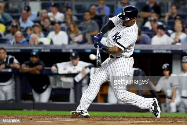 Aaron Hicks of the New York Yankees hits a single to right center field to score Todd Frazier against Trevor Bauer of the Cleveland Indians during...