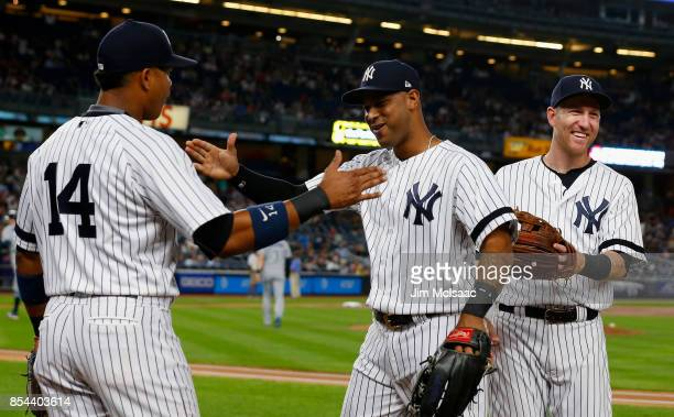 Aaron Hicks of the New York Yankees is met by teammates Starlin Castro and Todd Frazier of the New York Yankees after the first inning against the...