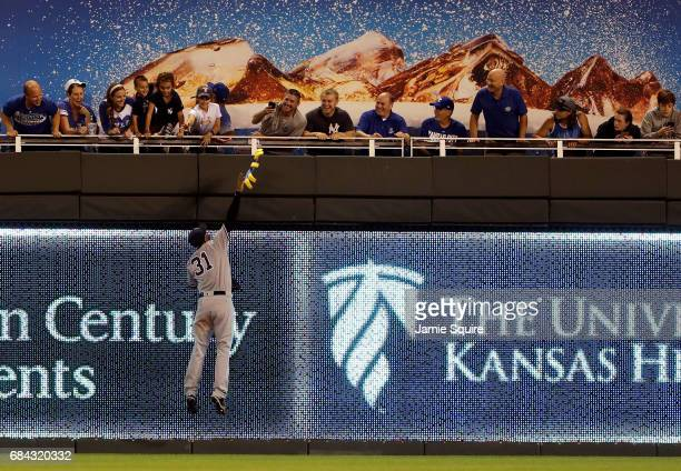 Aaron Hicks of the New York Yankees leaps to return a lost souvenir to a fan during the game against the Kansas City Royals at Kauffman Stadium on...